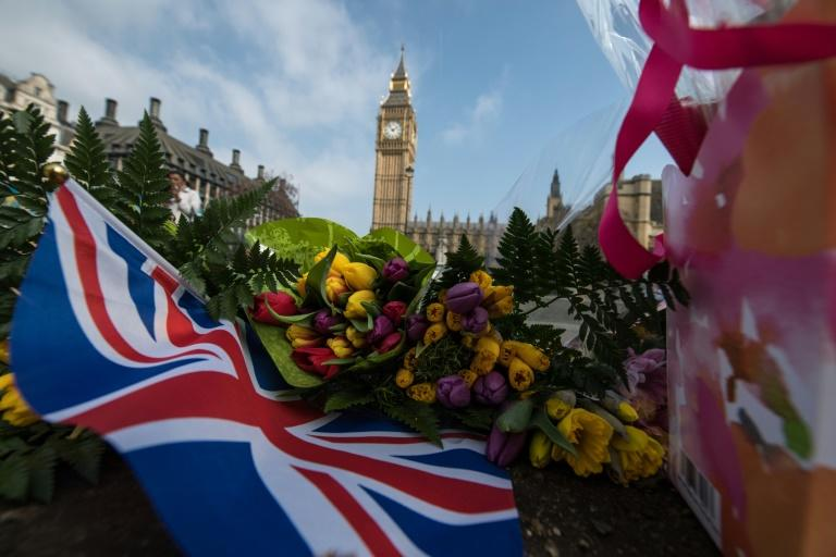 Floral tributes are seen in Parliament Square in front of the Houses of Parliament in central London on March 24, 2017, two days after the March 22 attack on the British parliament and Westminster Bridge
