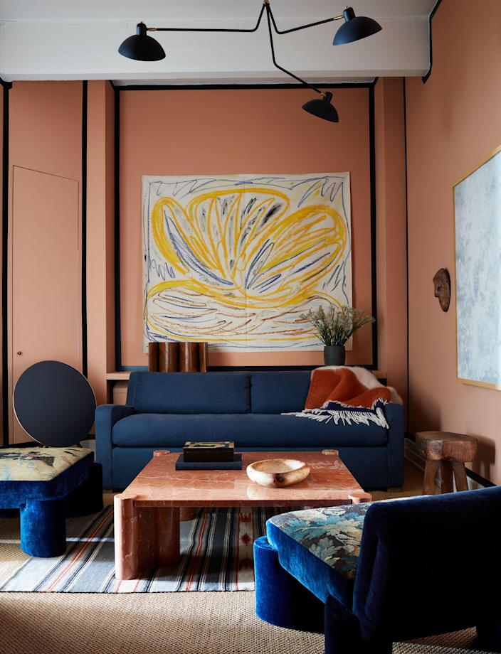 In the den, which is painted Dead Salmon from Farrow & Ball, with navy blue trim, a painting by Tamuna Sirbiladze (courtesy the artist and James Fuentes) hangs above a Restoration Hardware sofa with a Viso cashmere blanket. Marble coffee table by Gae Aulenti on a vintage Native American rug. Valle designed the tapestry chairs, and the painting at right is by Katherine Keltner. Speaker by Bang & Olufsen.