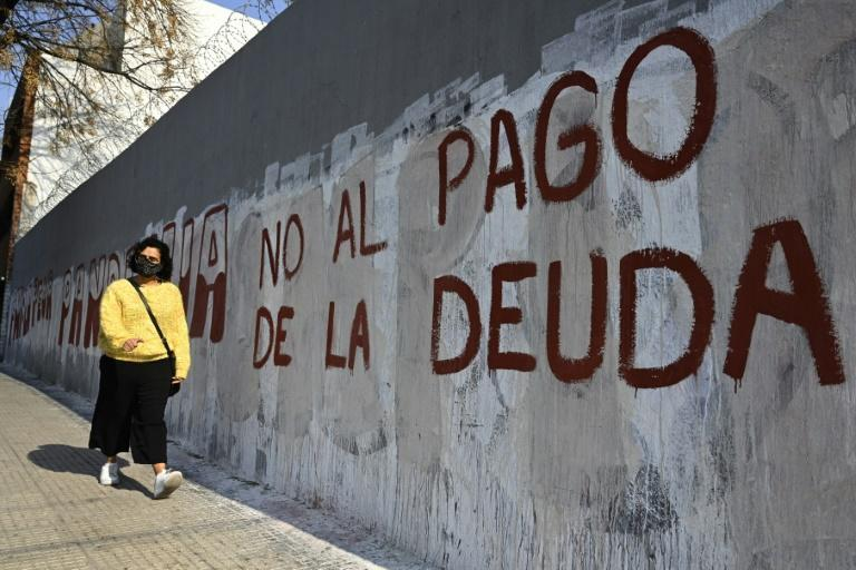 "A woman passes by a wall reading ""No to the debt payment"" in Buenos Aires, on August 3, 2020 -- the day before a deal was reached on restructuring of $66 billion of debt (AFP Photo/Juan MABROMATA)"