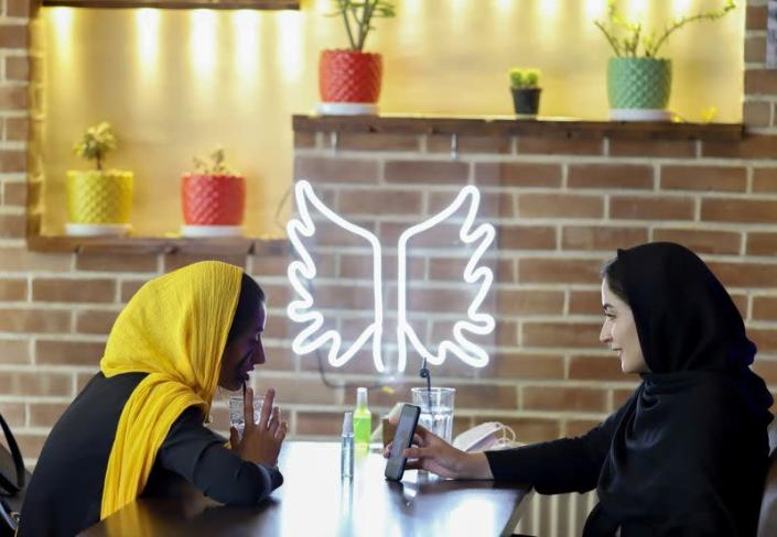 """Iranian women sit in a cafe after the launching of the """"Hamdam"""" dating app, in Tehran"""