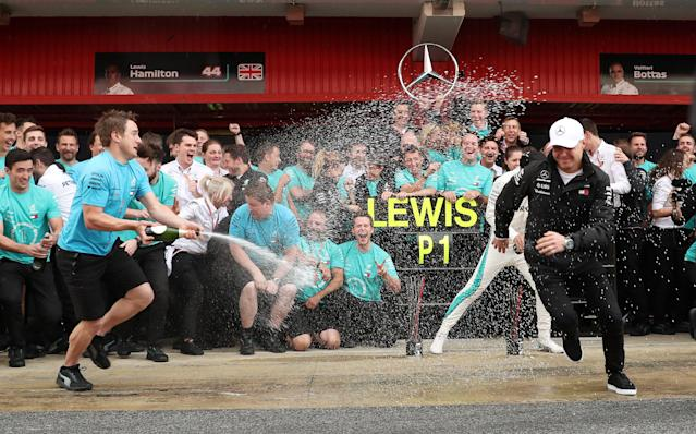 Formula One F1 - Spanish Grand Prix - Circuit de Barcelona-Catalunya, Barcelona, Spain - May 13, 2018 Mercedes' Lewis Hamilton and Valtteri Bottas are sprayed with champagne by a member of their team as they celebrate after finishing first and second respectively REUTERS/Albert Gea