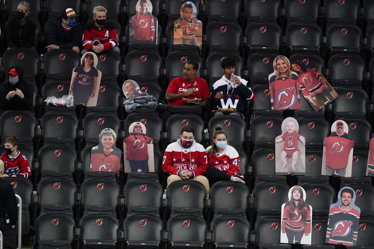 FILE - In this April 4, 2021, file photo, Washington Capitals fans sit among cutouts of New Jersey Devils fans as they watch the second period of an NHL hockey game between the Devils and the Capitals in Newark, N.J. Nearly half of new coronavirus infections nationwide are in just five states, including New Jersey — a situation that puts pressure on the federal government to consider changing how it distributes vaccines by sending more doses to hot spots. (AP Photo/Frank Franklin II)
