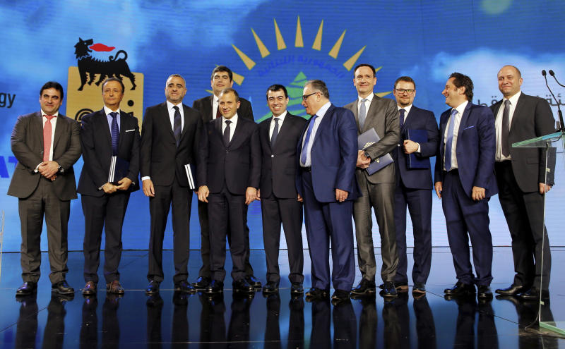 Lebanese foreign minister Gibran Bassil, fourth left, and Lebanese Energy and Water Minister Cesar Abi Khalil, center, pose for a photograph with representatives of oil companies Total, Eni, and Novatek and other officials after a ceremony held in Beirut, Lebanon, Friday, Feb. 9, 2018, during which Lebanon awarded the three companies with contracts to start exploratory offshore drilling for oil and gas. (AP Photo/Bilal Hussein)