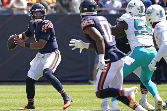 Chicago Bears quarterback Justin Fields, left, prepares to throw the ball against the Miami Dolphins during the second half of an NFL preseason football game in Chicago, Saturday, Aug. 14, 2021. (AP Photo/Nam Y. Huh)