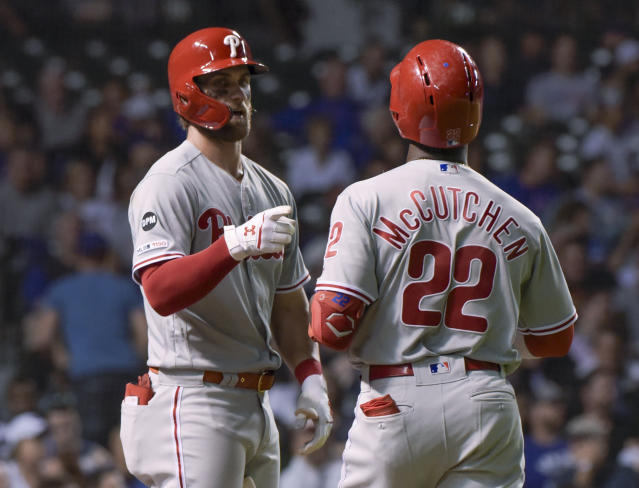 Philadelphia Phillies' Bryce Harper (3) congratulates Andrew McCutchen on his eighth-inning home run against the Chicago Cubs during a baseball game Wednesday, May 22, 2019, in Chicago. (AP Photo/Mark Black)