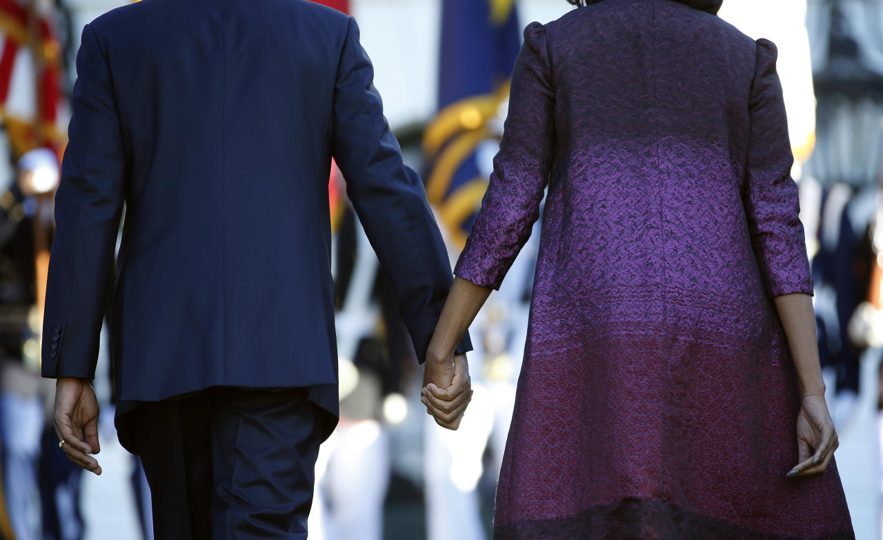 President Barack Obama and first lady Michelle Obama hold hands as they walk back to the White House in Washington, Tuesday, Sept. 11, 2012, after joining members of the White House staff during a moment of silence to mark the 11th anniversary of the Sept, 11th. (AP Photo/Carolyn Kaster)
