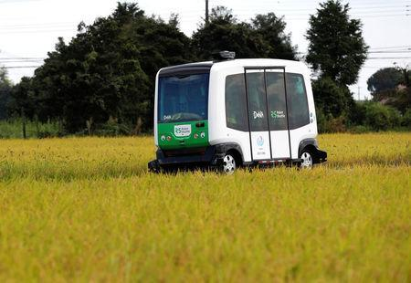 Robot Shuttle, a driver-less, self driving bus, developed by Japan's internet commerce and mobile games provider DeNA Co., drives past between rice stalk during an experimental trial with a self-driving bus in a community in Nishikata town, Tochigi Prefecture, Japan September 8, 2017. REUTERS/Issei Kato