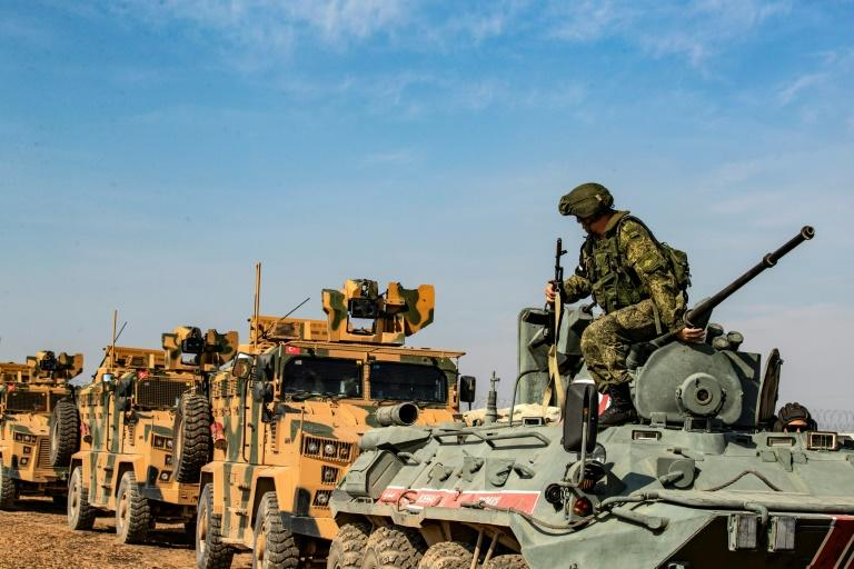 Turkish and Russian military vehicles carry out a joint patrol in the Syrian town of  Derbasiyeh