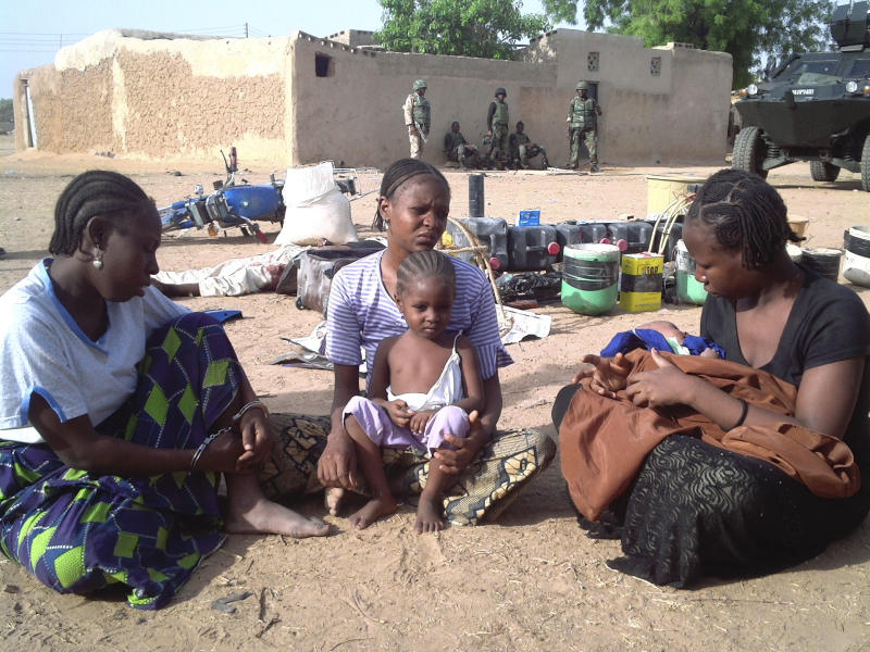 In this Photo taken Tuesday, May 1, 2012, mothers and children of suspected members of the sect known as Boko Haram sit outside their homes following a raid by soldiers at Bubugaje, Sharada neighborhood in Kano, Nigeria.  The radical Islamist sect Boko Haram published a video on the Internet Tuesday with images of a smiling suicide bomber, and containing threats against Nigerian journalists and newspapers. (AP Photos/Salisu Rabiu)