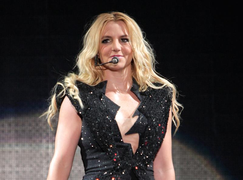 """FILE - In this Sept. 27, 2011 file photo, singer Britney Spears performs on a stage during a concert in Kiev, Ukraine, during her European Femme Fatale Tour. A source says she is joining Simon Cowell's singing contest as a judge on the singing competition series """"The X-Factor."""" (AP Photo/Leonid Naidiouk, file)"""