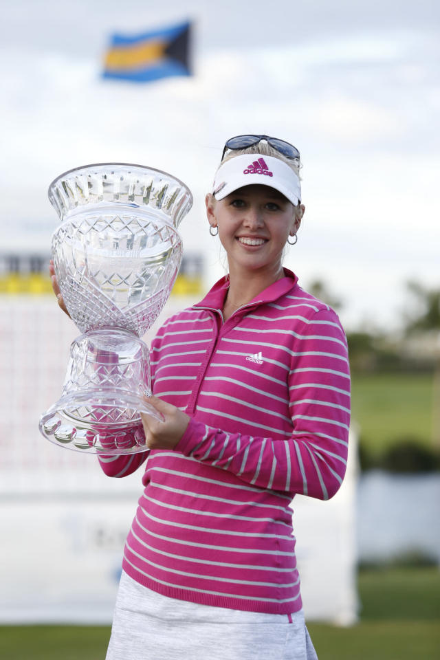 Jessica Korda of the U.S. holds her trophy as she poses for photographers following her victory at the LPGA Pure Silk Bahamas Classic at the Ocean Club Golf Course, Paradise Island, Bahamas, Sunday, Jan. 26, 2014. (AP Photo/Tim Aylen)