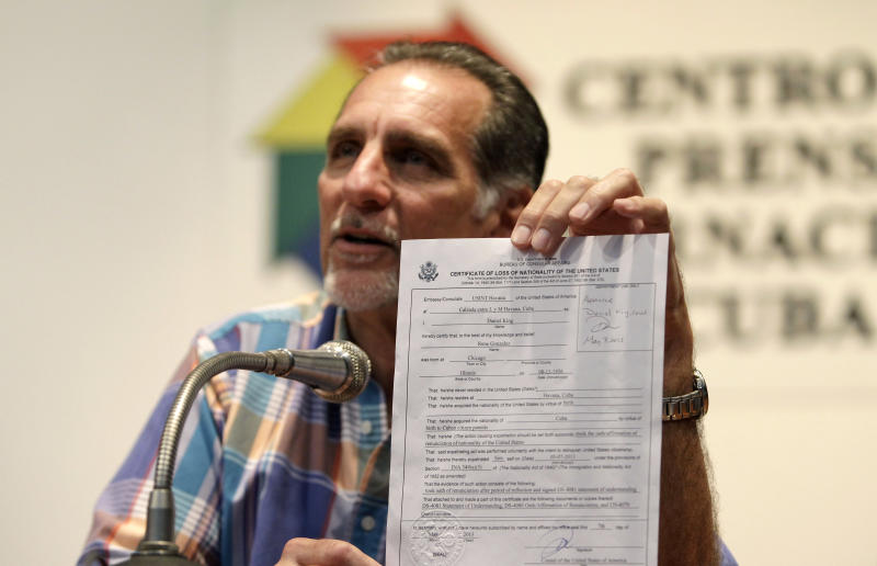 """Cuban agent Rene Gonzalez, 56, holds up his U.S. certificate of loss of nationality during a press conference in Havana, Cuba, Friday, May 10, 2013. Gonzalez who spent 13 years in a U.S. prison renounced his American citizenship Monday, May 6, 2013, as part of a deal that allows him to avoid returning to the United States to serve out the remainder of his probation. Gonzalez is one of the so-called """"Cuban Five"""" intelligence agents convicted in 2001 of spying on U.S. military installations in South Florida, exile groups and politicians. (AP Photo/Franklin Reyes)"""