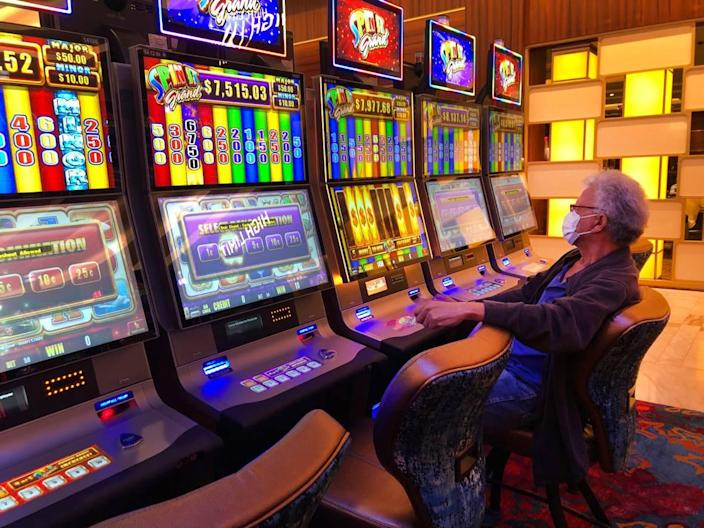 A patron wearing a mask plays a slot machine at the Seminole Hard Rock Hotel & Casino, Friday, March 20, 2020, near Hollywood, Fla.