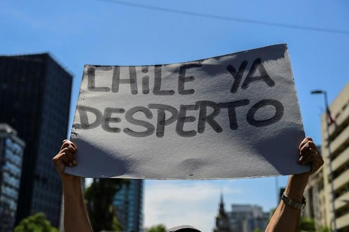 """A demonstrator in Santiago holds a sign reading """"Chile has awakened"""" (AFP Photo/Martin BERNETTI )"""