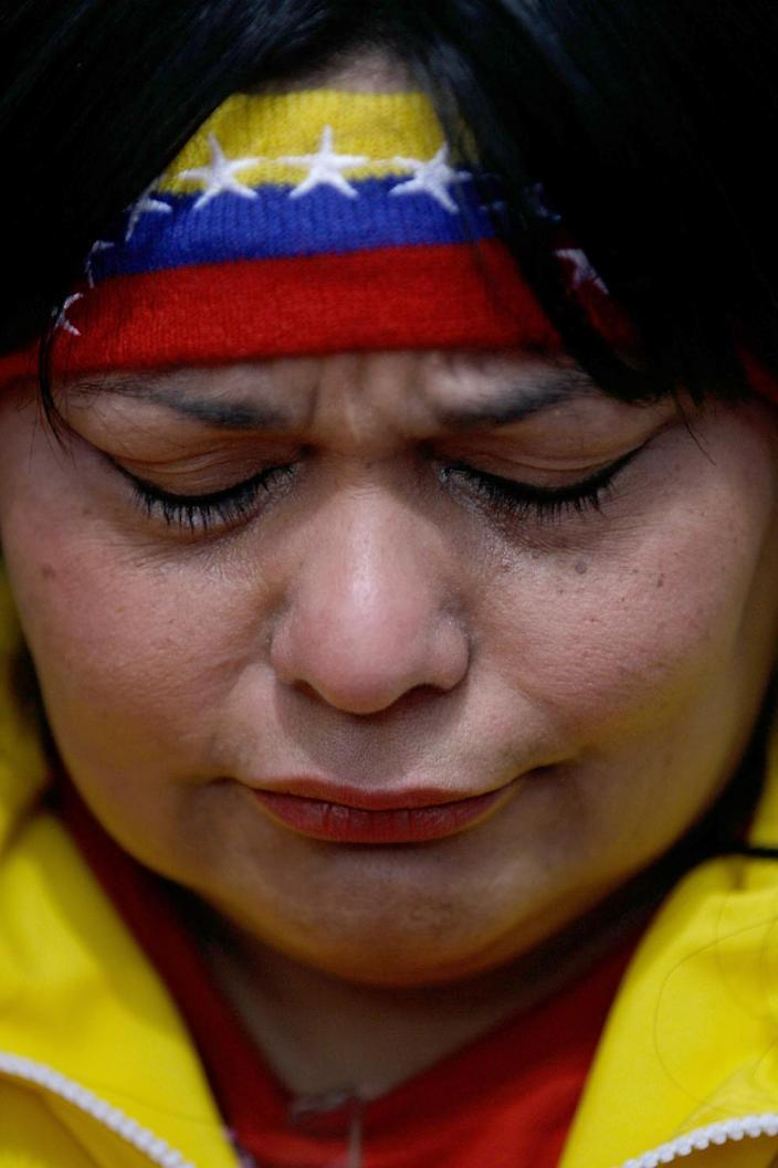 """A woman reacts during a demonstration in support of Venezuela's President Hugo Chavez at the Simon Bolivar square in Caracas, Venezuela, Sunday Dec. 9, 2012. Chavez was heading back to Cuba on Sunday for more cancer surgery after announcing that the illness returned despite two previous operations, chemotherapy and radiation treatment. Chavez said Saturday that if there are """"circumstances that prevent me from exercising the presidency further"""" Vice-President Nicolas Maduro should replace him for the remainder of his term.(AP Photo/Fernando Llano)"""