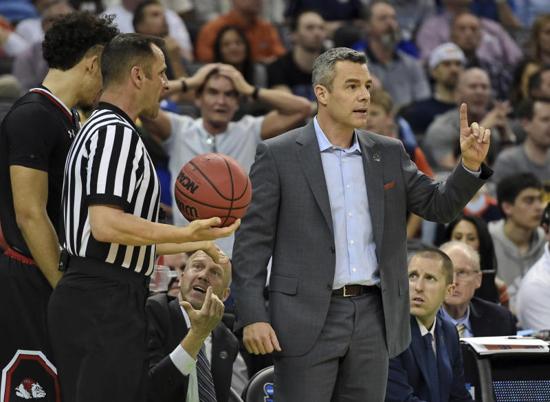Virginia head coach Tony Bennett, right, speaks to an official during a first-round game against Gardner-Webb in the NCAA mens college basketball tournament in Columbia, S.C. Friday, March 22, 2019. (AP Photo/Richard Shiro)
