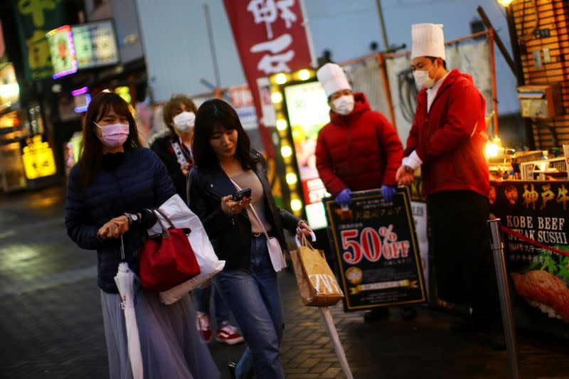 People, wearing protective masks following an outbreak of the coronavirus disease (COVID-19), walk on an almost empty street in the Dotonbori entertainment district of Osaka