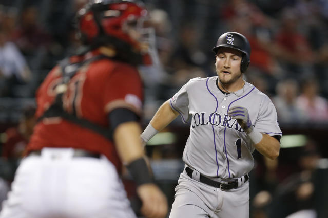 Colorado Rockies' Garrett Hampson (1) scores a run on a single by Tim Melville in the fourth inning during a baseball game against the Arizona Diamondbacks, Wednesday, Aug. 21, 2019, in Phoenix. (AP Photo/Rick Scuteri)