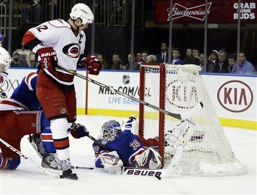New York Rangers goalie Henrik Lundqvist, of Sweden, stops a shot on the goal as Carolina Hurricanes' Eric Staal (12) skates past him during the first period of an NHL hockey game, Monday, March 18, 2013, in New York. (AP Photo/Frank Franklin II)