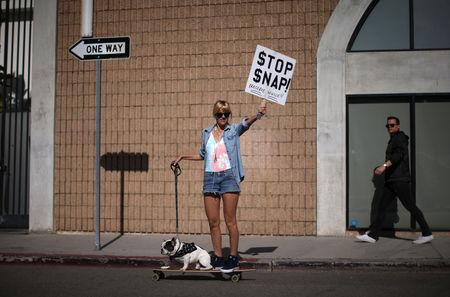 A woman protests outside a Snap Inc. office in Venice Beach as locals demonstrate on the street over the company moving into the beach community in Los Angeles, California, U.S. March 2, 2017 .  REUTERS/ Lucy Nicholson