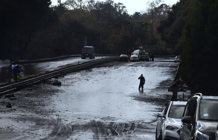 <p>A man wades in a flooded section of the US 101 freeway near the San Ysidro exit in Montecito, California on Jan. 9, 2018.<br> (Photo: Frederic J. Brown/AFP/Getty Images) </p>
