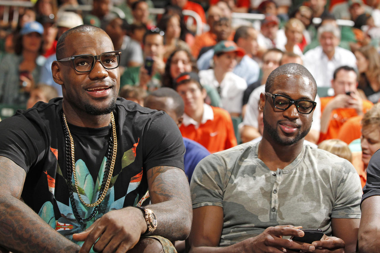 CORAL GABLES, FL - FEBRUARY 9: (L-R) Miami heat forward LeBron James and guard Dwyane Wade sit courtside during the game between the Miami Hurricanes and the North Carolina Tar Heels on February 9, 2013 at the BankUnited Center in Coral Gables, Florida. Miami defeated North Carolina 87-61. (Photo by Joel Auerbach/Getty Images)