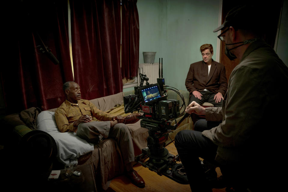 """This image released by Warner Bros. Entertainment shows director Steven Soderbergh, right, with actors, Don Cheadle, left, and Benicio Del Toro, right, on the set of """"No Sudden Move."""" (Claudette Barius/Warner Bros. Entertainment via AP)"""