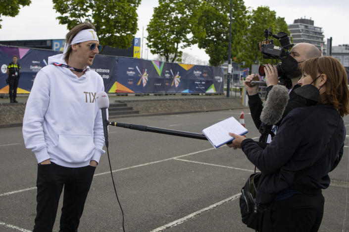 In this photo taken on May 15, 2021 Norway's Andreas Haukeland, known as TIX, is interviewed by Dutch national broadcaster NOS as he arrives for rehearsals at the Eurovision Song Contest at Ahoy arena in Rotterdam, Netherlands, Saturday, May 15, 2021. After last year's Eurovision Song Contest was canceled amid the global COVID-19 pandemic, it is roaring back to life with coronavirus bubbles added to its heady mix of music and camp. (AP Photo/Peter Dejong)