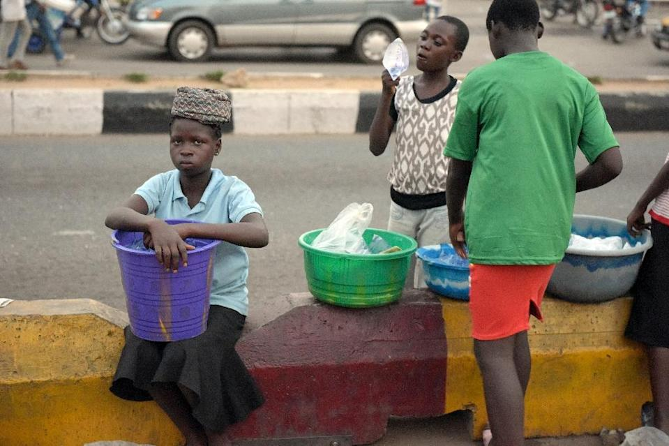 Children stand along the road to hawk their wares in Akure, southwestern Nigeria, on March 24, 2015 (AFP Photo/Pius Utomi Ekpei)