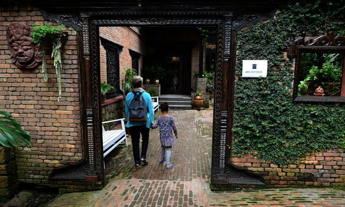 Seven-year-old blind girl who goes under the pseudonym Anna (R) walks with her adoptive mother at a restaurant in Kathmandu on July 23, 2014 (AFP Photo/Prakash Mathema)