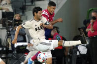 Los Angeles FC forward Carlos Vela, left, stops a shot from Dallas FC midfielder Bryan Acosta during the first half of an MLS soccer match Wednesday, June 23, 2021, in Los Angeles. (AP Photo/Marcio Jose Sanchez)