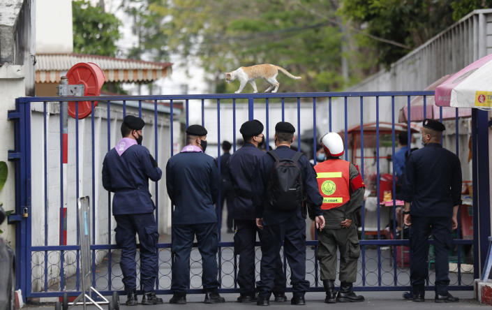 A cat walks on top of a gate at criminal court as the security persons wait for activists' arrival for a court procedure in Bangkok, Thailand, Monday, March 8, 2021. Prosecutors in Thailand charged 18 pro-democracy activists with sedition on Monday, while lodging additional charges of insulting the monarchy against three of them. (AP Photo/Sakchai Lalit)