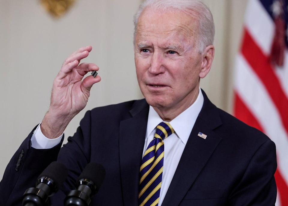 US President Joe Biden holds a chip as he speaks before signing an executive order aimed at addressing a global semiconductor shortage, in the State Dining Room at the White House in Washington, DC, on February 24. Photo: Reuters