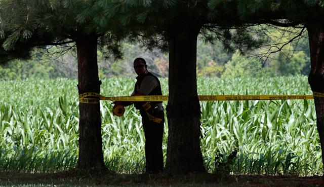 <p>An officer marks off the edge of a cornfield that borders the home of James Hodgkinson in Belleville, Ill., on Wednesday, June 14, 2017. (Photo: Robert Cohen/St. Louis Post-Dispatch via AP) </p>