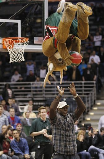 Bango, the Milwaukee Bucks' mascot, gets the ball from Green Bay Packers' Donald Driver and flips for a dunk in the second half of an NBA basketball game against the Detroit Pistons Monday, Jan. 30, 2012, in Milwaukee. (AP Photo/Jeffrey Phelps)