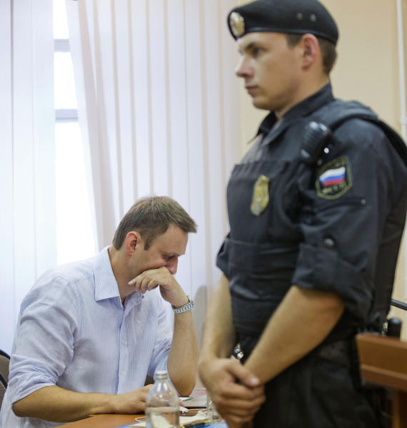 Russian opposition leader Alexei Navalny, left, reads documents in a court in Kirov, Russia on Friday, July 5, 2013. A prosecutor on Friday asked the Russian court to convict Navalny of embezzlement and sentence him to six years in prison. Navalny, who led protests against President Vladimir Putin and exposed alleged government corruption, is accused of heading a criminal group that embezzled 16 million rubles ($500,000) worth of timber from a state-owned company while working as an adviser to the provincial governor in Kirov in 2009. (AP Photo/Evgeny Feldman)
