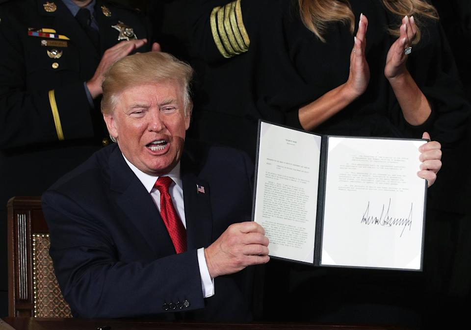 U.S. President Donald Trump shows a presidential memorandum that he signed during an event highlighting the opioid crisis in the U.S. October 26, 2017 in the East Room of the White House in Washington, DC. He signed the bipartisan opioid legislation two days prior. (Photo: Alex Wong/Getty Images)