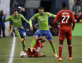 Seattle Sounders' Marco Pappa, left, and Clint Dempsey, center, step over FC Dallas' Zach Loyd, left, as Je-Vaughn Watson (27) looks on in the first half of an MLS western conference semifinal soccer match, Monday, Nov. 10, 2014, in Seattle. (AP Photo/Ted S. Warren)