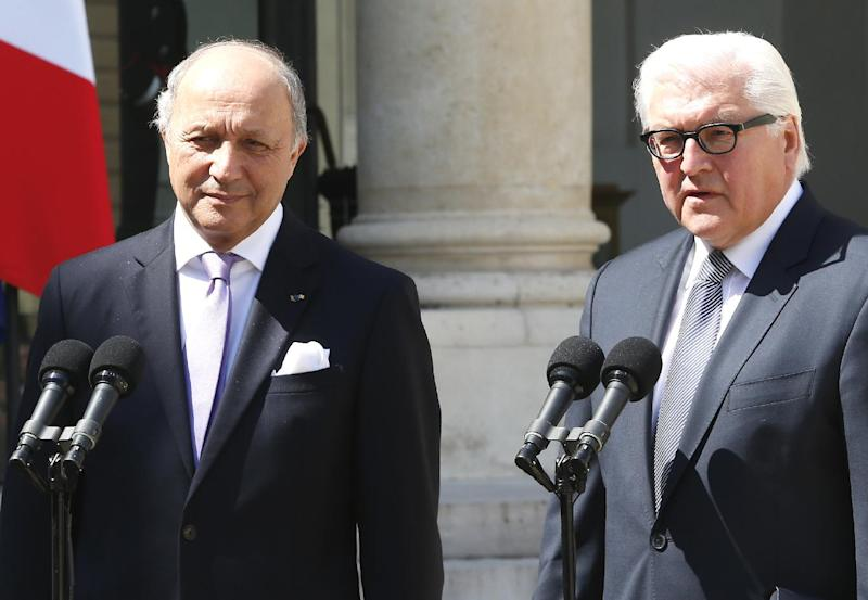 French Foreign Minister Laurent Fabius, left, and German counterpart Frank-Walter Steinmeier, right, talks to reporters after a weekly Cabinet meeting in the Elysee Palace in Paris, Wednesday, May 14, 2014.(AP Photo/Jacques Brinon)