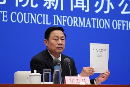 "Guo Weimin, Vice Director of the Information Office of China's State Council holds a white paper titled ""China's Position on the China-US Economic and Trade Consultations"" at a news conference in Beijing"