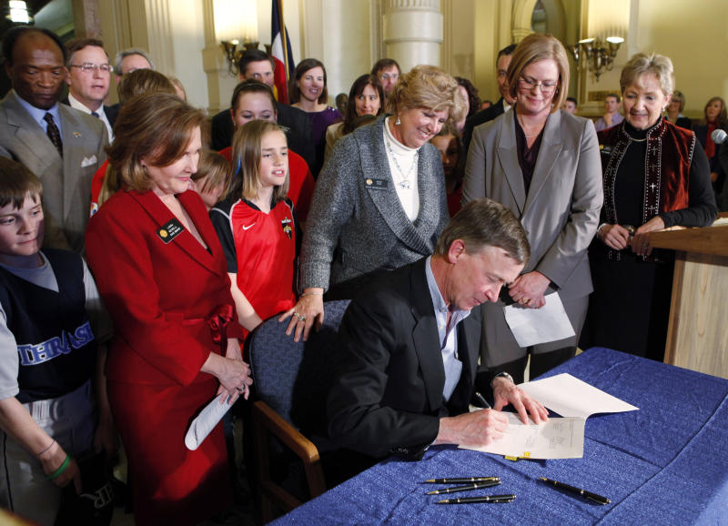 Gov. John Hickenlooper after he signs Senate Bill 40, named after Jake Snakenberg at the Capitol in Denver on Tuesday, March 29, 2011. Jake Snakenberg, a Colorado high school student died in 2004 after being hit during a football game. His family said doctors told him his injury was likely compounded by a concussion he suffered in a previous game that went undiagnosed. (AP Photo/Ed Andrieski)