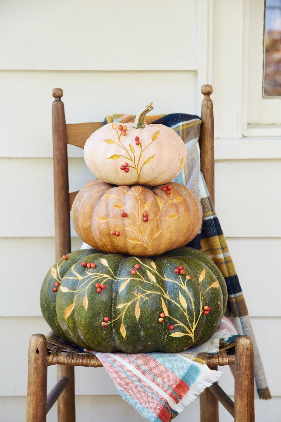 <p>The perfect sophisticated decor for greeting guests to your front door. Place directly on the porch or layer on a vintage ladderback chair with different color plaid blankets.</p><p><strong>To make:</strong> Purchase one large, one medium, and one small pumpkin (any color combo works) that stack nicely. Remove the stems from the large and medium pumpkin. Lightly sketch a vine pattern on a pumpkin with a pencil. Use a linoleum carving tool to etch out the pattern. Once complete attach red berries or beads with hot glue.</p>
