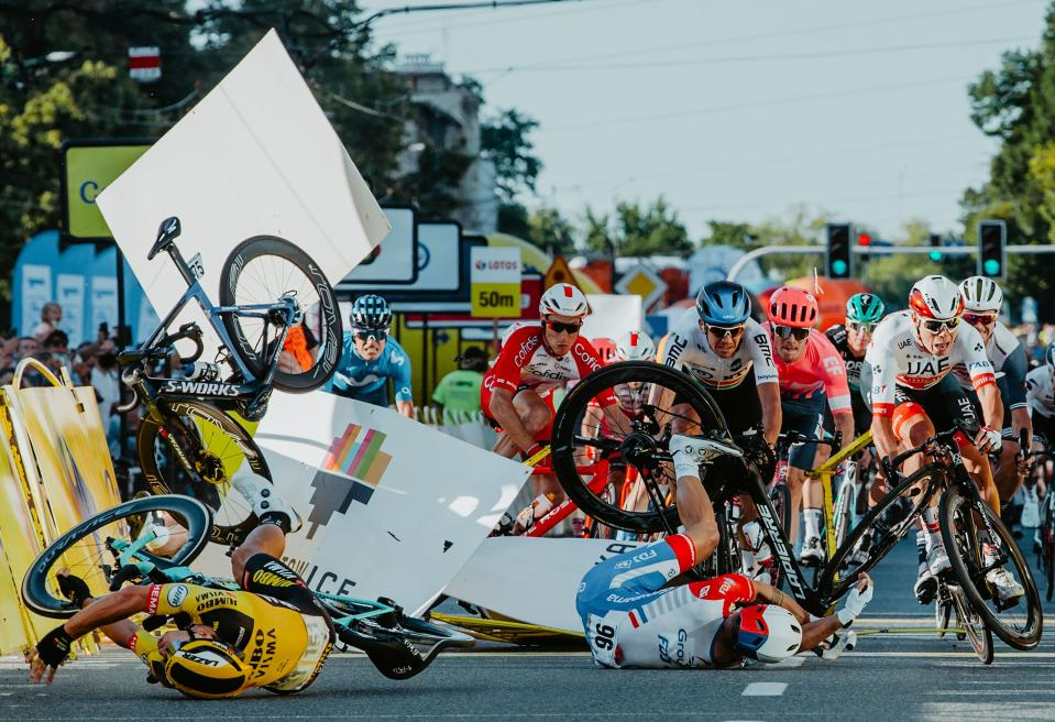 TOPSHOT - Dutch cyclist Fabio Jakobsen's bicycle (behind,L) flies through the air as he collides with compatriot Dylan Groenewegen (on the ground ,L) during the opening stage of the Tour of Poland race in Katowice , southern Poland on August 5, 2020. - The Dutch rider was fighting for his life on Wednesday after he was thrown into and over a barrier at 80km/h in a sickening conclusion to the opening stage of the Tour of Poland. (Photo by Szymon Gruchalski / Forum / AFP) (Photo by SZYMON GRUCHALSKI/Forum/AFP via Getty Images)