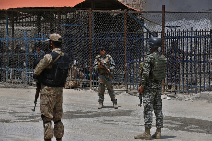 Pakistan and Afghan soldiers stand guard at Torkham border crossing, in Khyber district, Pakistan, Tuesday, Aug. 3, 2021. Pakistan's military said it completed 90 percent of the fencing along the border with Afghanistan, vowing the remaining one of the most difficult tasks of improving the border management will be completed this summer to prevent any cross-border militant attack from both sides. (AP Photo/Anjum Naveed)