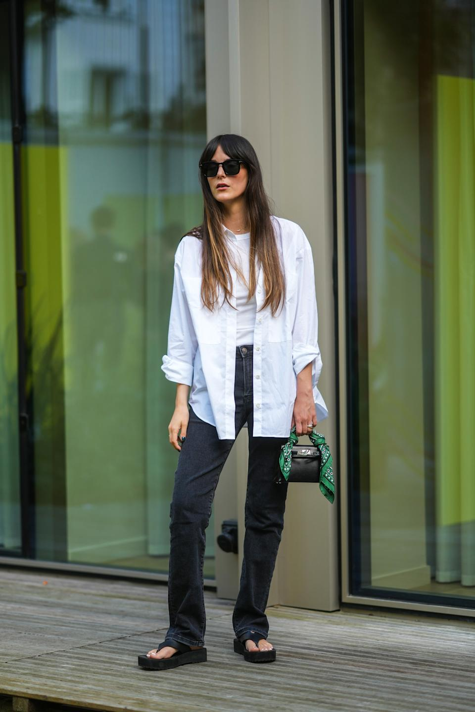 PARIS, FRANCE - JULY 01: Leia Sfez wears sunglasses, a white t-shirt, a white oversized shirt, black denim jeans pants, a black leather mini Hermes Kelly bag with attached green scarf, sandals / flip-flops, during the Twilly By Hermes : Launch Party In Paris, on July 01, 2021 in Paris, France. (Photo by Edward Berthelot/Getty Images)