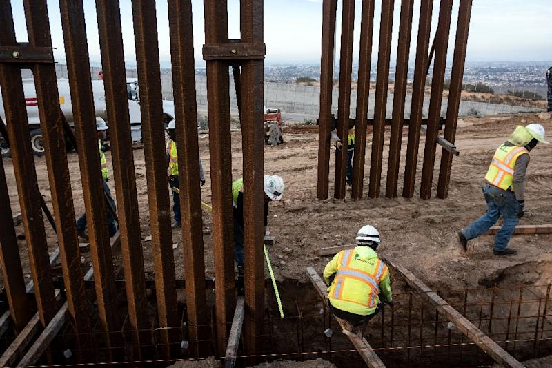A construction crew works on replacing the US-Mexico border fence south of San Diego, California