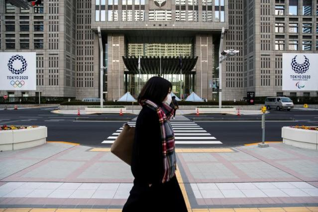 FILE PHOTO: A woman wearing a protective face mask, following an outbreak of the coronavirus, walks past banners of the upcoming Tokyo 2020 Olympic and Paralympic Games outside the Tokyo Metropolitan Government building in Tokyo