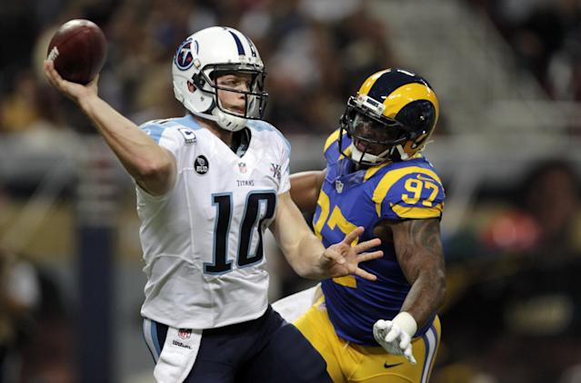Tennessee Titans quarterback Jake Locker, left, throws under pressure from St. Louis Rams defensive end Eugene Sims during the second quarter of an NFL football game Sunday, Nov. 3, 2013, in St. Louis. (AP Photo/Tom Gannam)