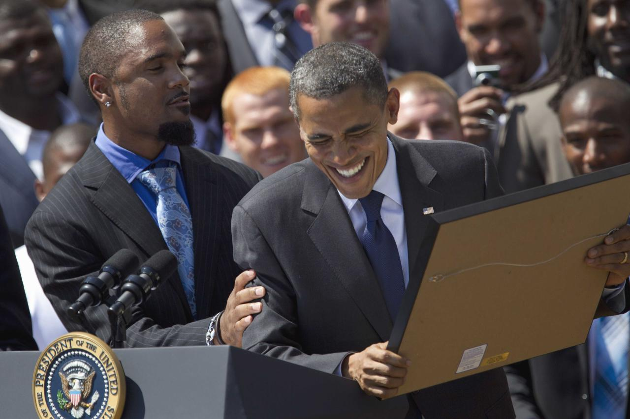 President Barack Obama reacts to be presented a stock certificate by Green Bay Packers football cornerback Charles Woodson, left, during a ceremony honoring the Super Bowl XLV Champion Green Bay Packers, Friday, Aug. 12, 2011, on the South Lawn of the White House in Washington. On the far right is team General Manager Ted Thompson. (AP Photo/Carolyn Kaster)