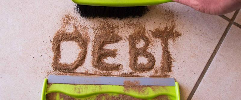 Sweep debt clean concept with debt written in dirt on a floor and a person is about to sweep the debt dirt in a dust pan using a small hand broom
